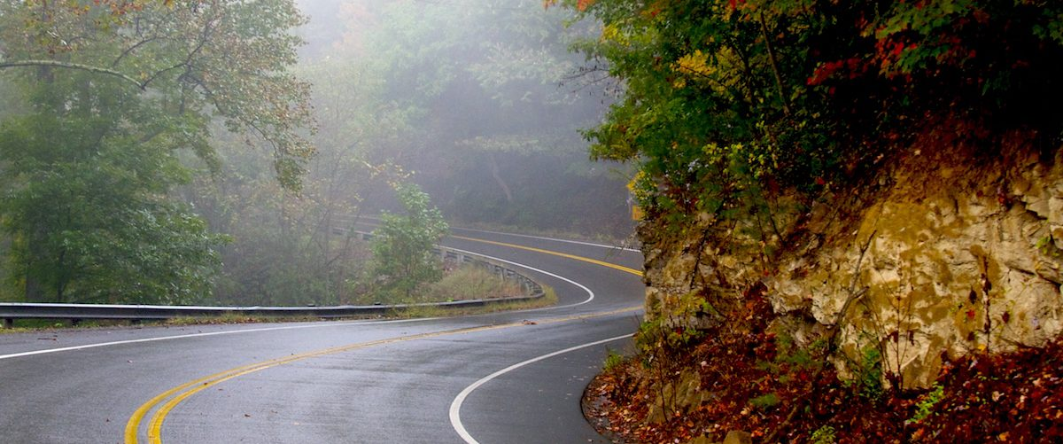 A curving country road winds past a pale cliff and forest in West Virginia