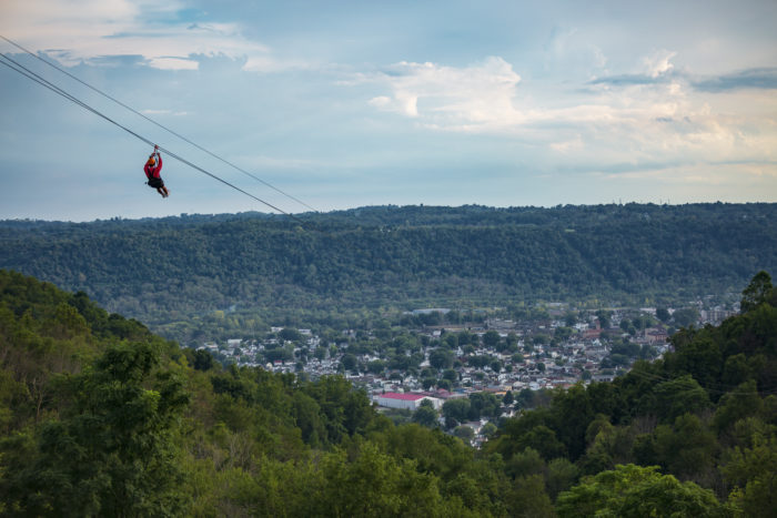 A zipline over a forested valley with houses and buildings in the distance