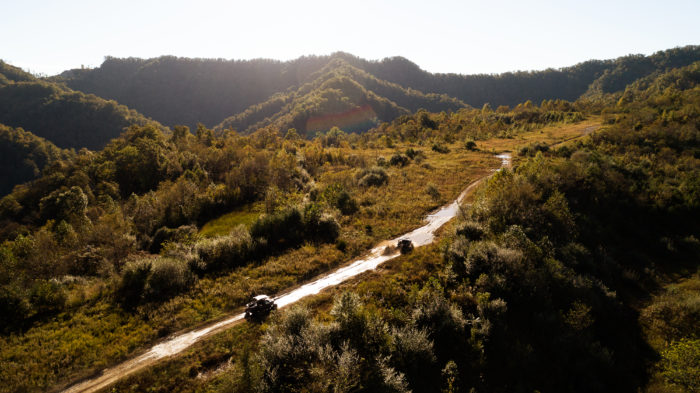 Two ATVs driving down long dirt stretch surrounded by grassy hills and trees