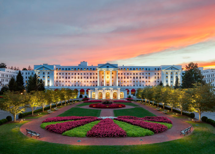 The Greenbrier resort during sunset with colorful gardens and lawns lit up in front