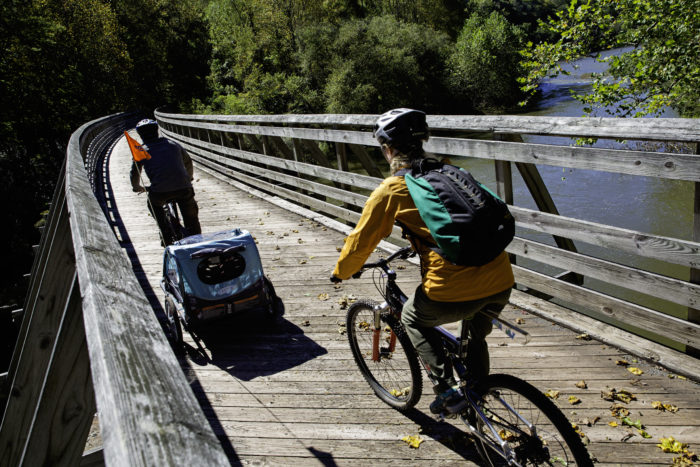 Two bikers on a wooden bridge over a river, one bike towing a small baby carrier